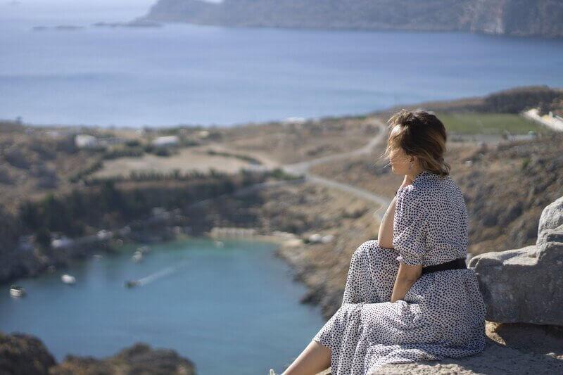 Женщина сидит на скале на фоне моря
