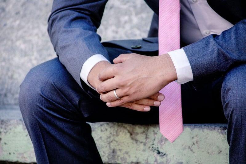 Человек в костюме с розовым галстуком