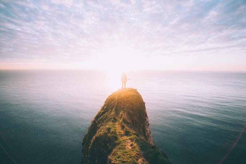 Человек на горном пике в свете солнца