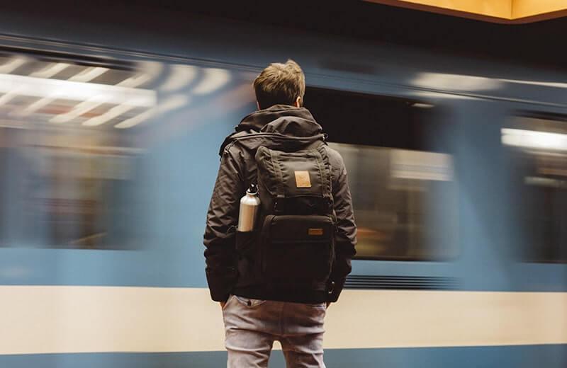 Мужчина с рюкзаком проезжающий поезд