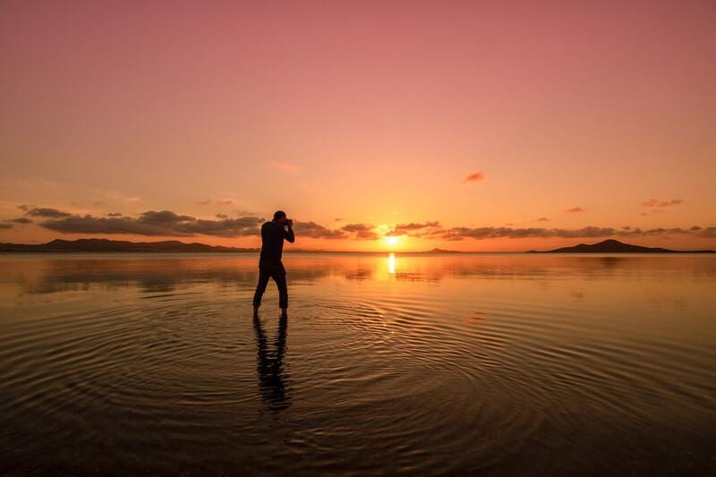 Человек в море фотографирует закат