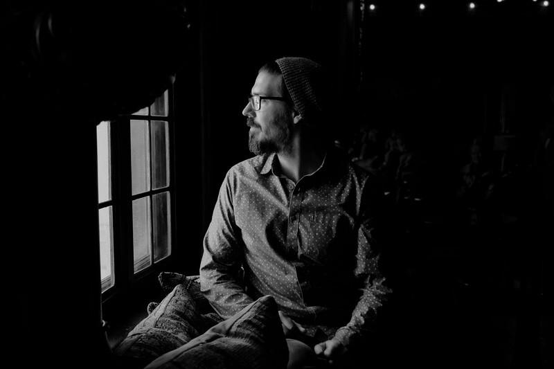 Мужчина у окна в темной комнате