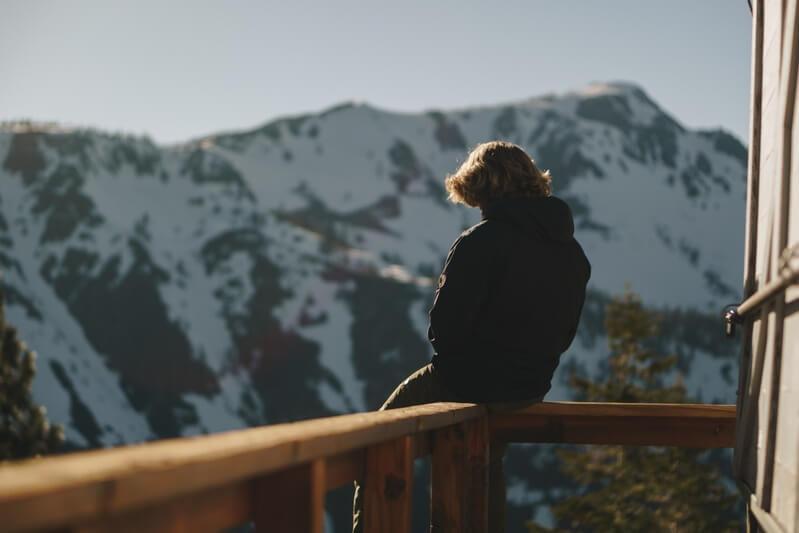 Парень сидит на парапете на фоне гор
