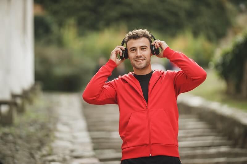 Мужчина в красном слушает музыку в наушниках