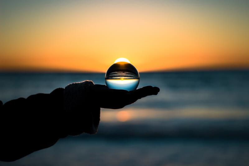 Хрустальный шар в руке на фоне заката