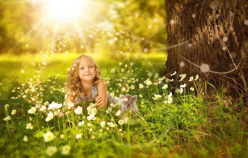 Девочка в траве возле дерева
