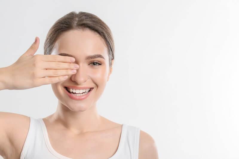 Девушка закрывает один глаз рукой