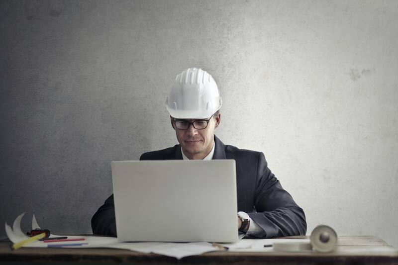 Мужчина в каске ноутбук