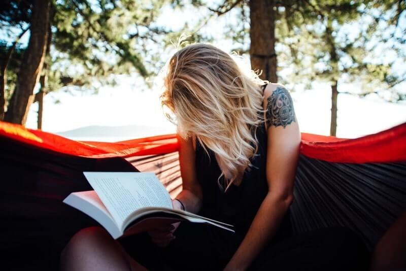 Женщина в гамаке читает книгу
