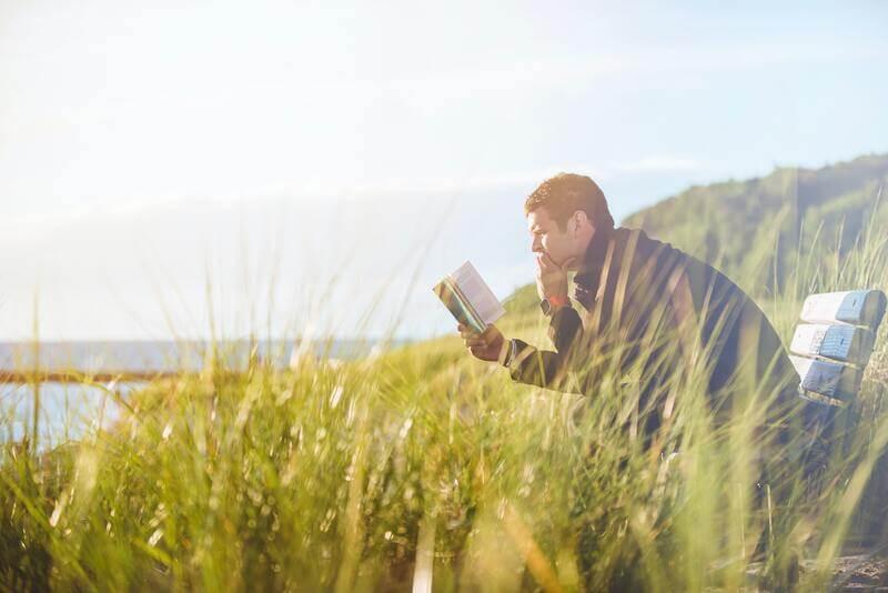 Мужчина на природе читает книгу